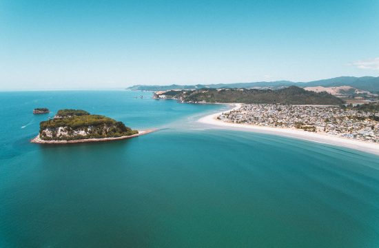 a drone photo looking across whangamata beach to donut island
